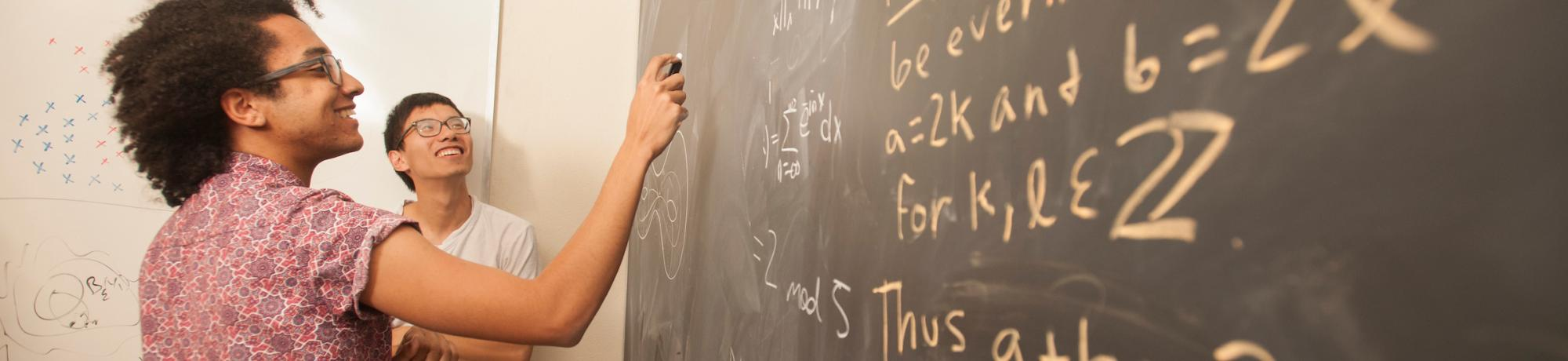 Students writing math equations on a chalkboard